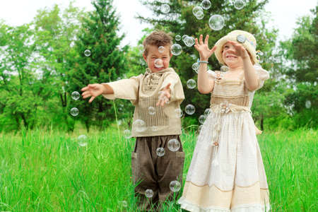 Cute little boy and girl is playing with big bubbles outdoor. photo