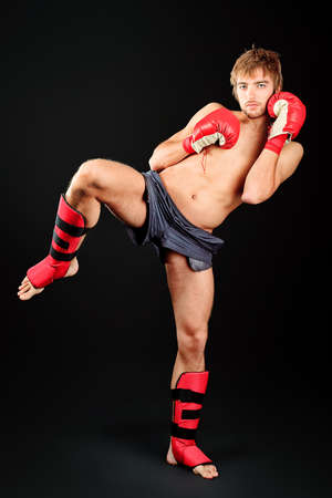 Portrait of a handsome boxer in red gloves posing at studio. photo