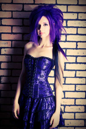 Portrait of a punk girl posing over brick wall. photo