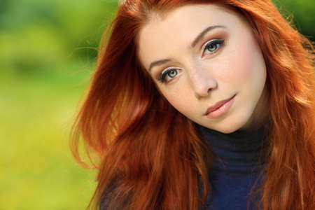 redhead: Portrait of a beautiful red-haired young woman outdoors. Stock Photo