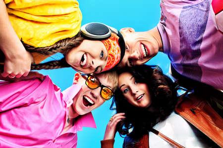 Vrolijke jonge mensen lachen over de blauwe hemel. Stockfoto