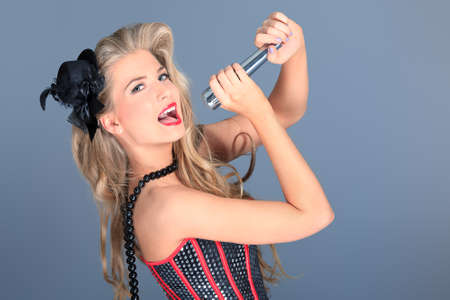 temptative: Portrait of a charming blonde woman singing with microphone in studio.