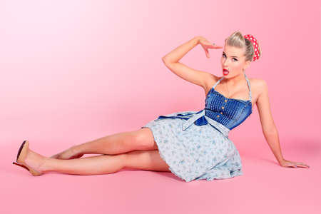 pinup: Beautiful young woman with pin-up make-up and hairstyle posing over pink background. Stock Photo