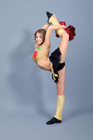 Beautiful girl cheerleader posing at studio.  photo