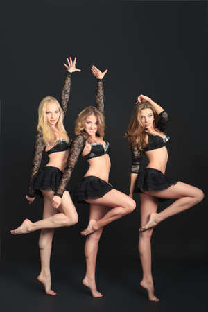 sexy dancer: Group of professional cheerleaders posing at studio. Over black background.