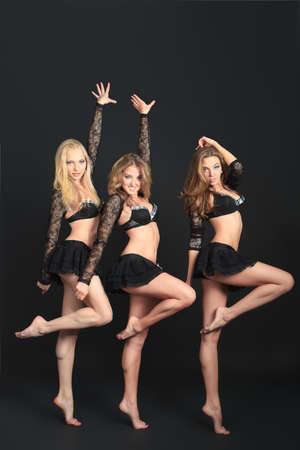 black cheerleader: Group of professional cheerleaders posing at studio. Over black background.