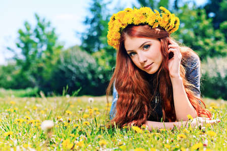 Romantic young woman in a circlet of flowers outdoors. photo