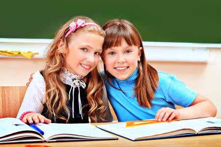 school life: Portrait of two happy schoolgirls in a classroom.