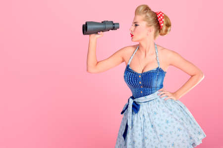 50s adult: Beautiful young woman with pin-up make-up and hairstyle looking through binoculars.