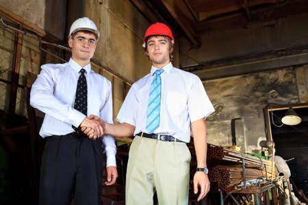 coincidir: Tema industrial: dos negocios haciendo la asociación en un área de fabricación.