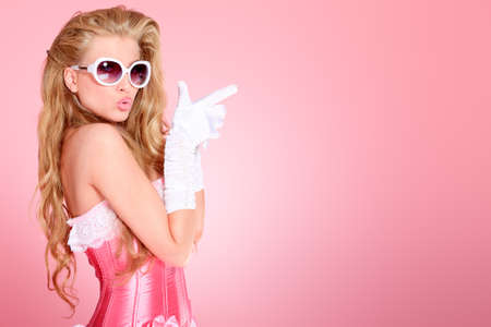 pink posing: Portrait of a charming blonde woman posing in studio over pink background.
