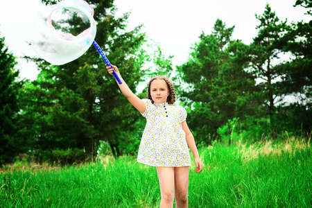 Happy girl is playing with big bubbles in a park. photo