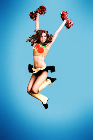 Beautiful girl cheerleader jumping in victory. Studio shot.  photo