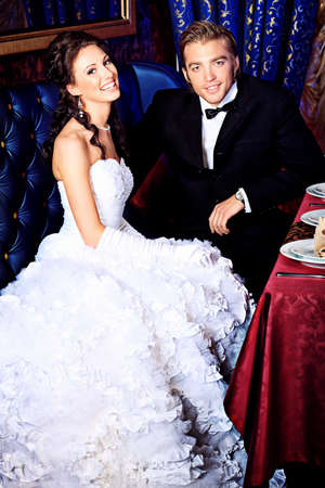 Charming bride and groom on their wedding celebration in a luxurious restaurant. photo