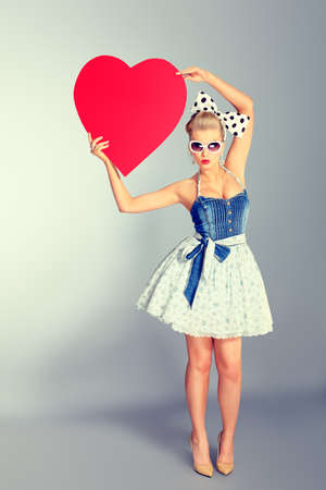 50s fashion: Beautiful young woman with pin-up make-up and hairstyle posing in studio with red hearts.