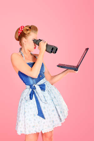 Attractive pin-up girl looking through binoculars to her laptop. photo