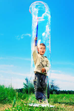 big game: Cute little boy is playing with big bubbles outdoor. Stock Photo