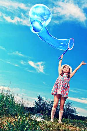 burbujas de jabon: Feliz niña está jugando con burbujas de gran tamaño en un parque.