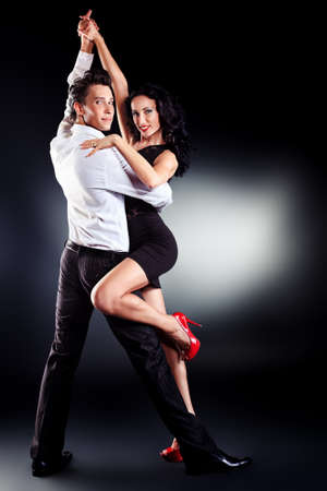 dance pose: Beautiful couple of professional artists dancing passionate dance. Stock Photo
