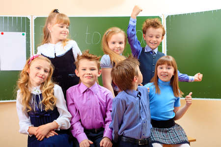 Happy schoolchildren at a classroom. Education. Stock Photo