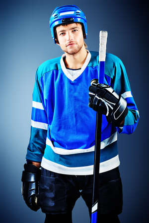 Portrait of a handsome ice-hockey player with hockey stick. Studio shot. photo