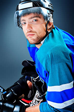 icehockey: Portrait of a handsome ice-hockey player. Studio shot.
