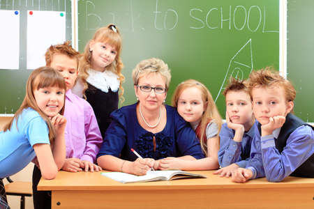 the pupil: Happy schoolchildren with their teacher at a classroom. Education.