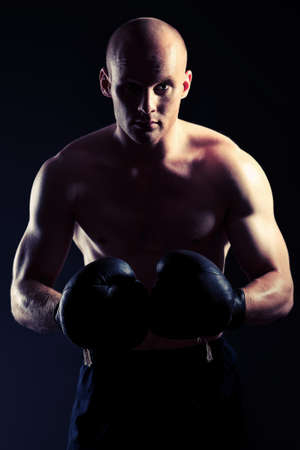 Portrait of an aggressive boxer in gloves posing at studio. photo