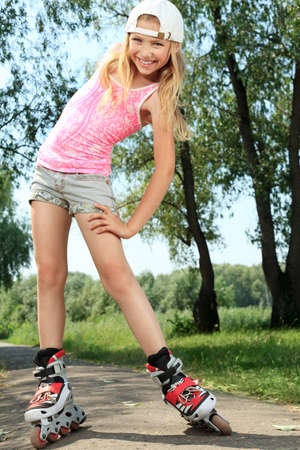 adolescence: Cute girl in roller skates at a park.