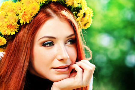 Portrait of a romantic young woman in a circlet of flowers outdoors. photo