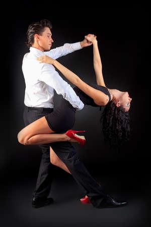 Beautiful couple of professional artists dancing passionate dance. photo