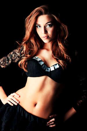 porrista: Hermosa niña porrista posando en el estudio. Fondo negro.