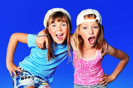 Twee vrolijke meisjes buiten over blauwe hemel.