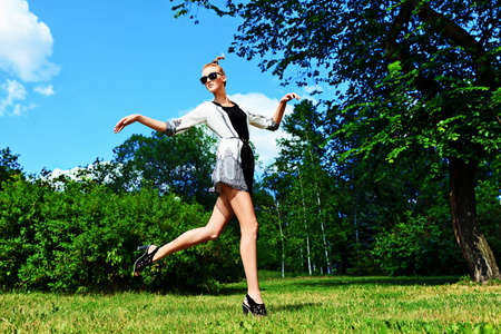 Fashion woman running in the summer park. photo
