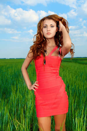 Beautiful woman posing in the meadow over blue sky. Stock Photo - 14693711