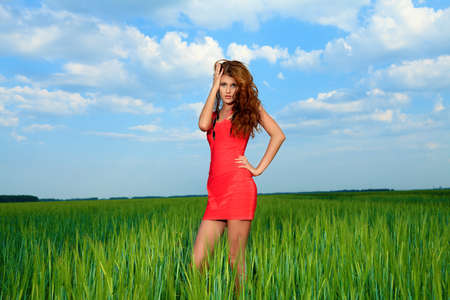 Beautiful woman posing in the meadow over blue sky.