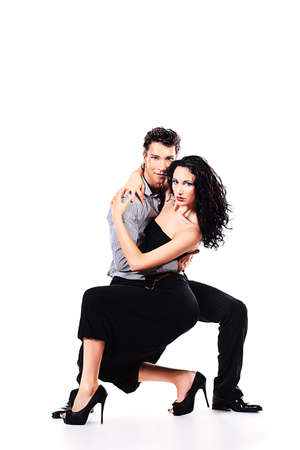dancing pose: Beautiful couple of professional artists dancing passionate dance. Isolated over white. Stock Photo
