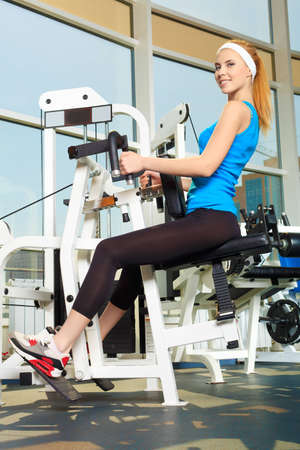 Young sporty woman doing exercises in the gym centre. Stock Photo - 14730919