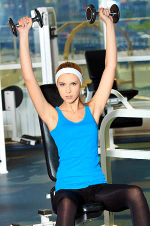 Young sporty woman doing exercises in the gym centre. Stock Photo - 14730907