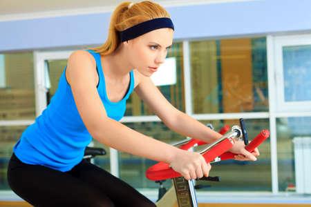 haciendo ejercicio: Una mujer joven haciendo ejercicio deportivo en bicicleta en el centro de gimnasio. Foto de archivo