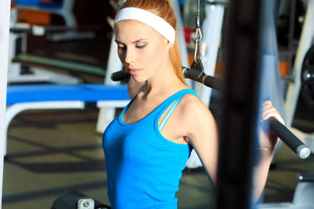 Young sporty woman doing exercises in the gym centre. Stock Photo - 14730903