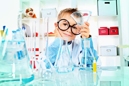 experiment: Cute boy is making science experiments in a laboratory. Education. Stock Photo
