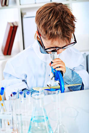 Cute boy is lookingin his microscope in a laboratory. Education. photo