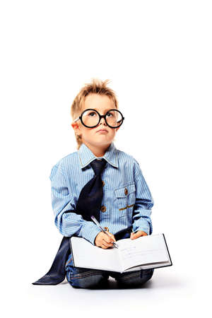 Portrait of a little boy in spectacles reading a book. Isolated over white background. Stock Photo - 14748164
