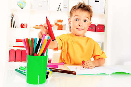 Little boy drawing in his notebook at home. photo