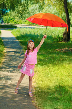 Happy summer girl with umbrella outdoors. Stock Photo