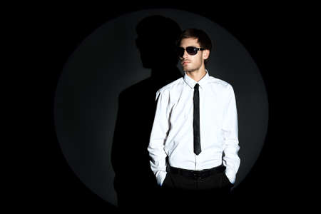 formal clothing: Portrait of a handsome man over black background.