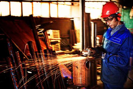 mechanical men: An industrial background. Welder in a factory