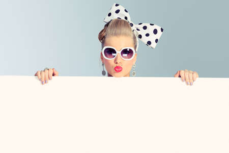 retro fashion: Beautiful young woman with pin-up make-up and hairstyle posing in studio with white board.