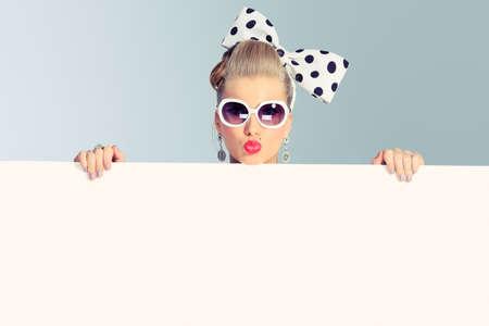 móda: Krásná mladá žena s pin-up make-up a účes představuje ve studiu s bílou tabuli. Reklamní fotografie